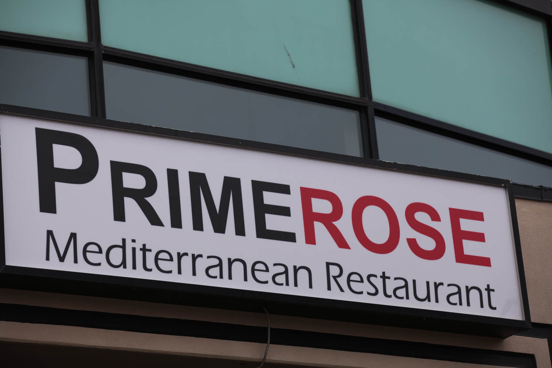 Image shows the Primerose Mediterranean Restuarant sign above the front entrance as seen from teh car park.