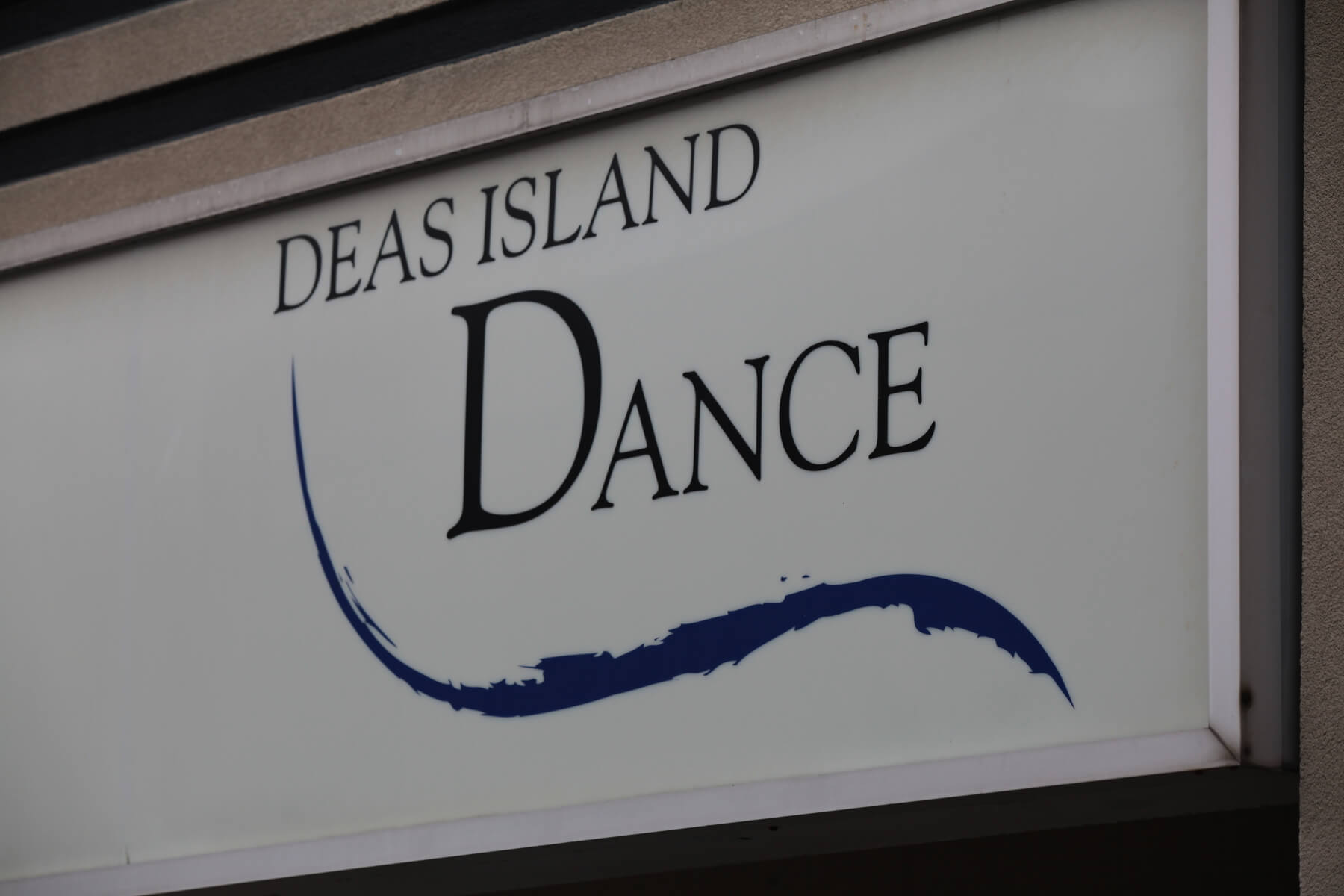 Image shows the Deas Island Dance sign above the front entrance as seen from teh car parking.