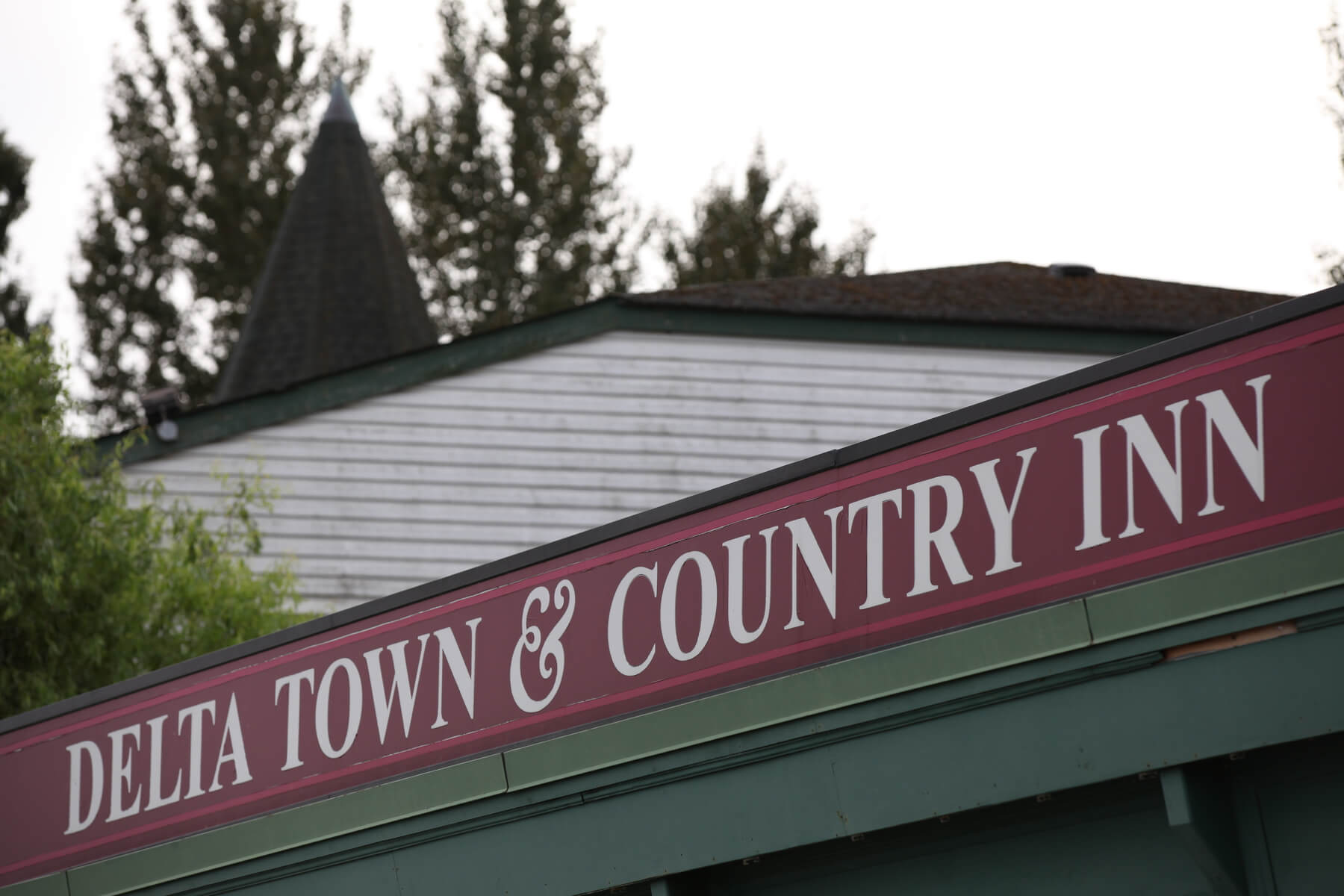 Image shows the Delta Town & Country Inn signage located above the front entrance to the hotel as seen from the car park.